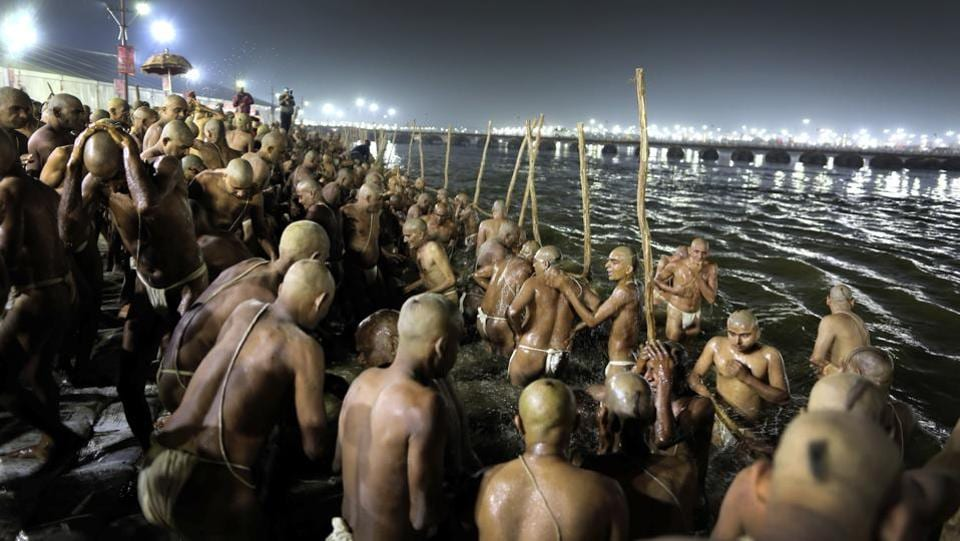 "Hindu men take a dip for becoming Naga Sadhus. Usually the ritual is performed only after a person dies. But the last ""Pind Dan"" at the Naga initiation ceremony is for the sadhu himself, symbolizing the unity of his soul with God. (Rajesh Kumar Singh / AP)"