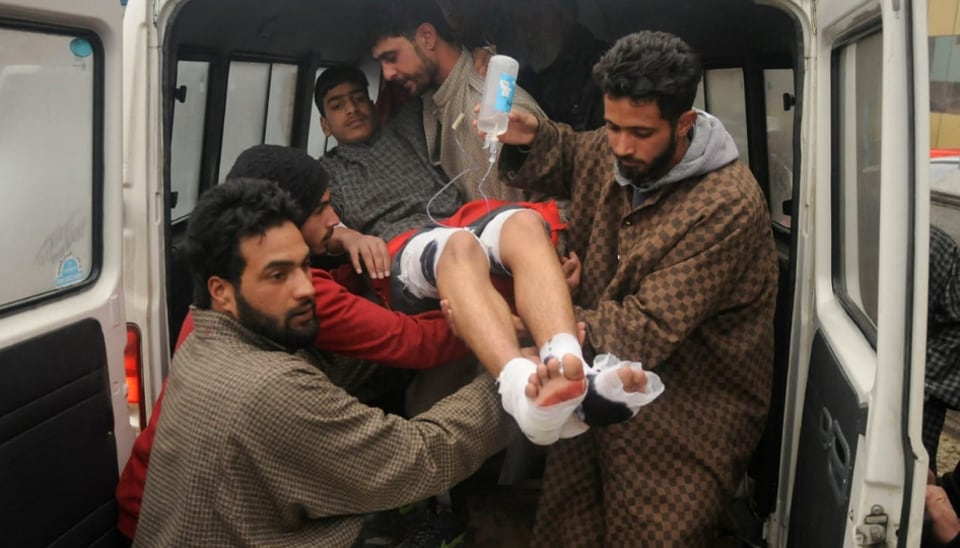 Relatives and locals carry a student who was among 12 injured in a blast in a school in Pulwama for treatment  to a hospital in Srinagar on  Wednesday.