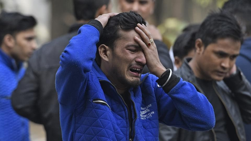 A man breaks down after getting the news of his brother's death at the fire in Karol Bagh's Arpit Palace hotel, in New Delhi, India, on Tuesday, February 12, 2019.