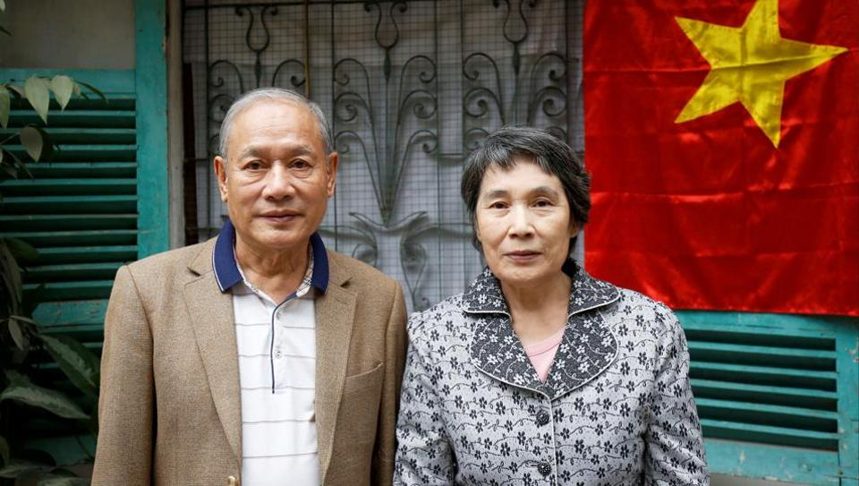 Former Vietnamese chemical student Pham Ngoc Canh who studied in North Korea and his North Korean wife Ri Yong Hui stand in front of their house while posing for a photo in Hanoi, Vietnam February 12.