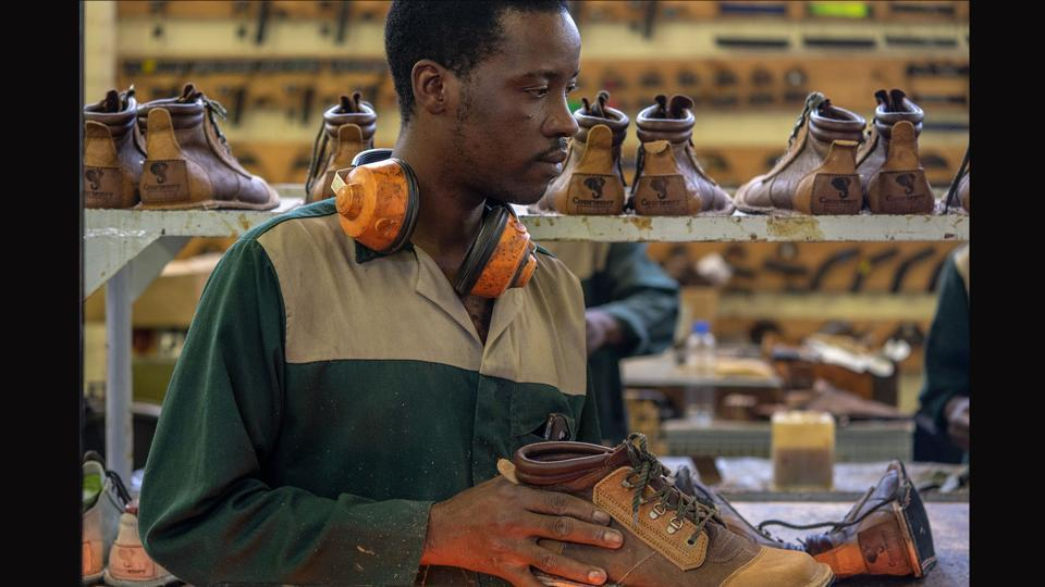 An employee of the Courteney boot company applies wax on shoes on the production line in Zimbabwe's Bulawayo city. Founded in 1993, the firm has recently ramped up production to just 30 pairs a day, all of them made meticulously by 14 employees in a one-room workshop. Exporting mostly to the US, Europe, Britain and South Africa, the boots are paid for in precious US dollars -- a key to survival in Zimbabwe's economy as it lurches downwards.  (Zinyange Auntony / AFP)