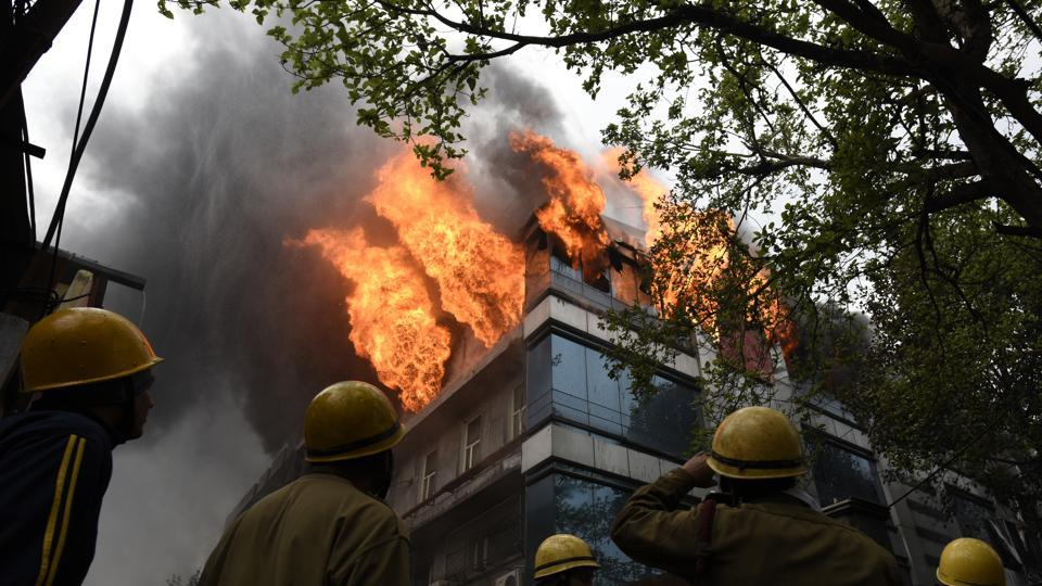 Fumes of smoke seen as firefighters try to douse the fire that broke out early morning at a card manufacturing factory, at Naraina Industrial area, in New Delhi. According to the fire department, no casualty has been reported yet. (Sanchit Khanna / HT Photo)