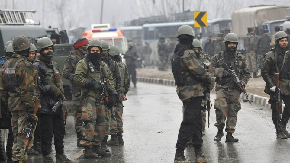 Secuirty forces near the damaged vehicles at Lethpora on the Jammu-Srinagar highway.