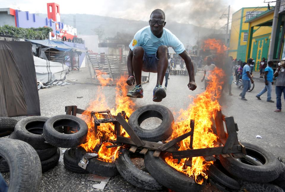 A protester jumps over a burning barricade during a protest against the government in the streets of Port-au-Prince, Haiti. (Jeanty Junior Augustin / REUTERS)