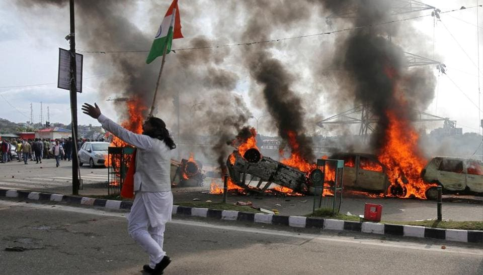 A demonstrator reacts next to burning cars during a protest against the attack on a bus that killed 44 Central Reserve Police Force (CRPF) personnel in south Kashmir on Thursday, in Jammu February 15, 2019.
