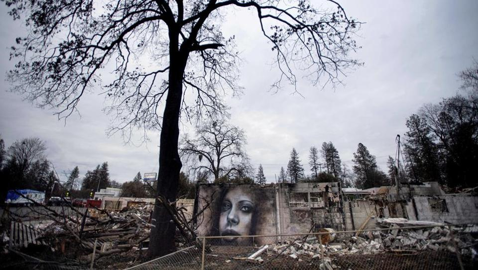 A mural by artist Shane Grammer adorns the wall of a building leveled by the Camp Fire in Paradise, California. Grammer says he painted murals throughout the fire-ravaged town to convey hope in the midst of destruction. In the 100 days since a wildfire nearly burned the town of Paradise off the map, the long recovery is just starting. (Noah Berger / AP Photo)