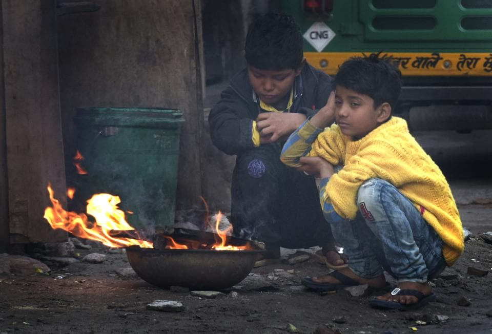 Children sit near fire to protect themselves from cold on a winter morning, at Indraprastha Extension, in New Delhi, India, on Sunday, January 27, 2019.