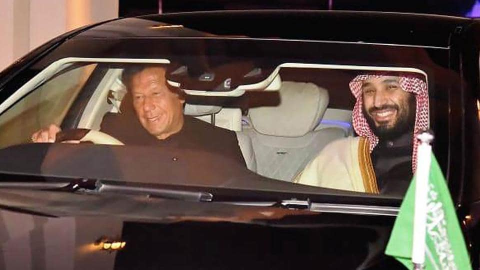 Pakistan's Prime Minister Imran Khan (L) drives a car next to Saudi Arabian Crown Prince Mohammed bin Salman (R) upon his arrival at the military Nur Khan Air Force base in Islamabad.