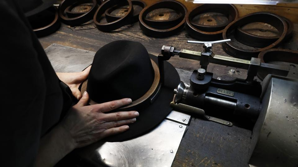 A man holds a hat inside the Borsalino hat factory. To relaunch Borsalino, Camperio has brought in a team of fashion experts, including former Gucci CEO Giacomo Santucci. The expansion plan foresees selling more in the United States and Asia and developing new collections to appeal to younger generations and to women, two key growth markets. (Antonio Calanni / AP Photo)