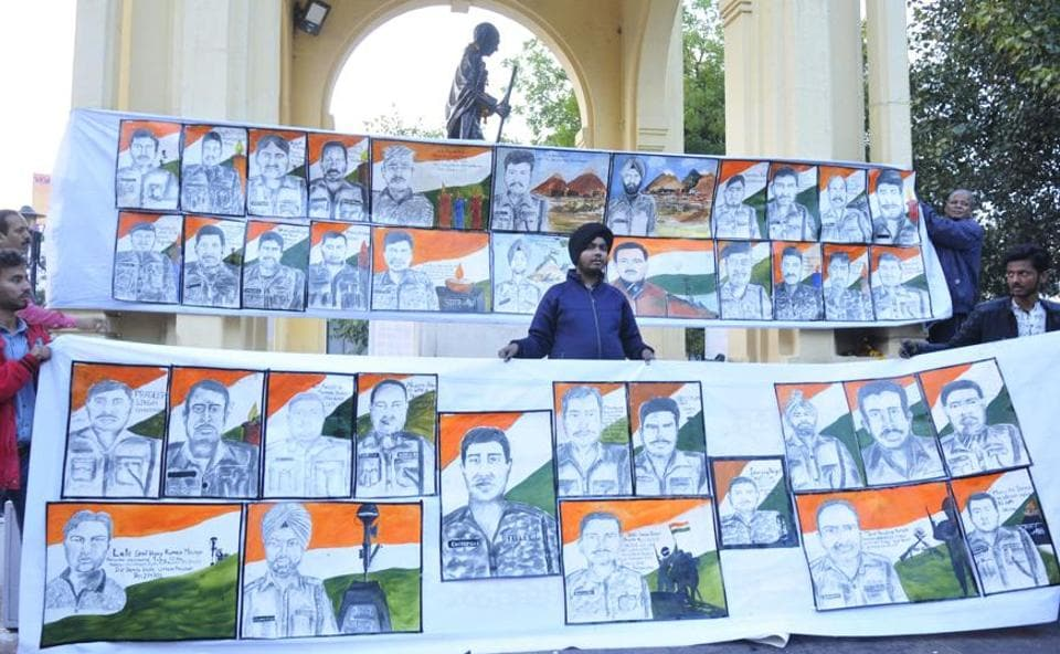 Aman Singh Gulati with the portraits of the CRPF personnel killed in J&K.