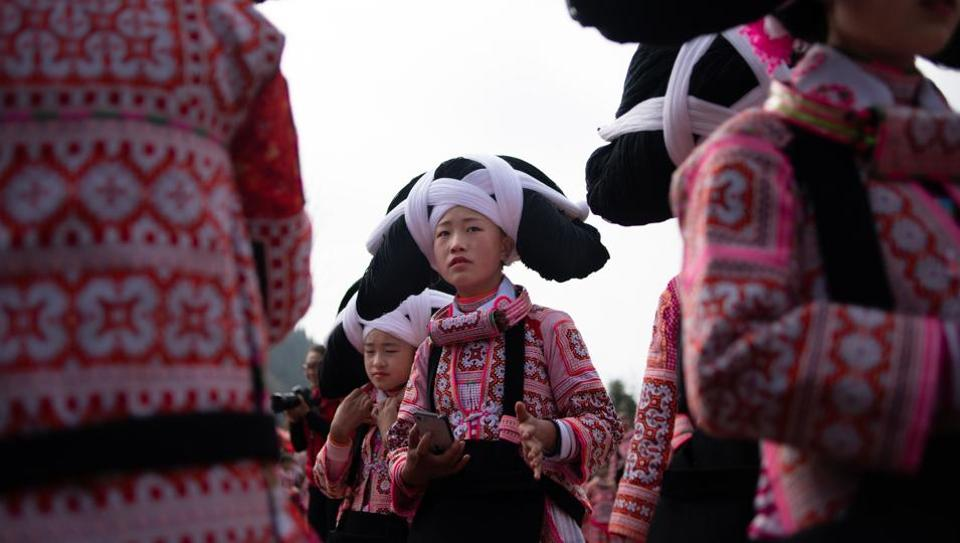 Girls from the Long Horn Miao, a branch of the Miao ethnic minority group, prepare to take part in the annual flower festival or 'Tiaohuajie' in the village of Longjia in China's Guizhou province. - Against a stunning mountain backdrop, dozens of girls and women of the Long Horn Miao ethnicity performed for the annual celebration held in Guizhou province on the 10th day of the Lunar New Year -- the Year of the Pig. (Fred Dufour / AFP )