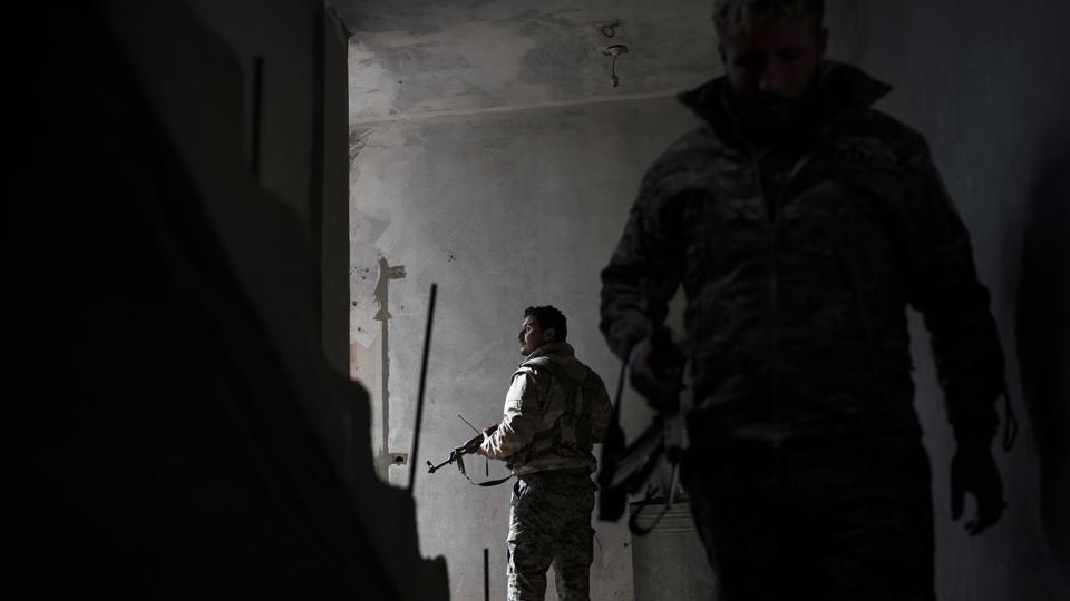 US-backed Syrian Democratic Forces (SDF) fighters walk in a building as fight against Islamic State militants continue in the village of Baghouz, Syria. The Islamic State group has been reduced from its self-proclaimed caliphate that once spread across much of Syria and Iraq at its height in 2014 to a speck of land on the countries' shared border. (Felipe Dana / AP)