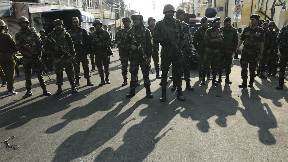 Indian Army soldiers watch a clash between policemen and protestors during curfew in Jammu.