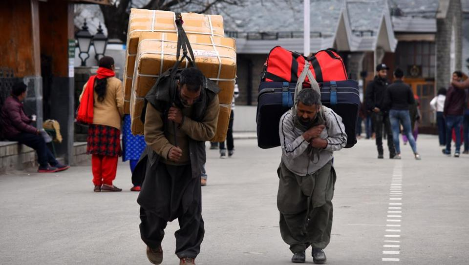 After terror attack on CRPF convoy in Pulwama in Jammu and Kashmir Kashmiri migrant labourers carry luggage. (Representative image)