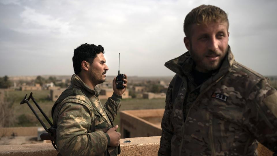 SDF fighters talk on a radio in a rooftop position as fight against Islamic State militants continues. The SDF can't assault the site or call in airstrikes because of the civilians. The fighters have seen the militants moving civilians around at gunpoint as protection. (Felipe Dana / AP)