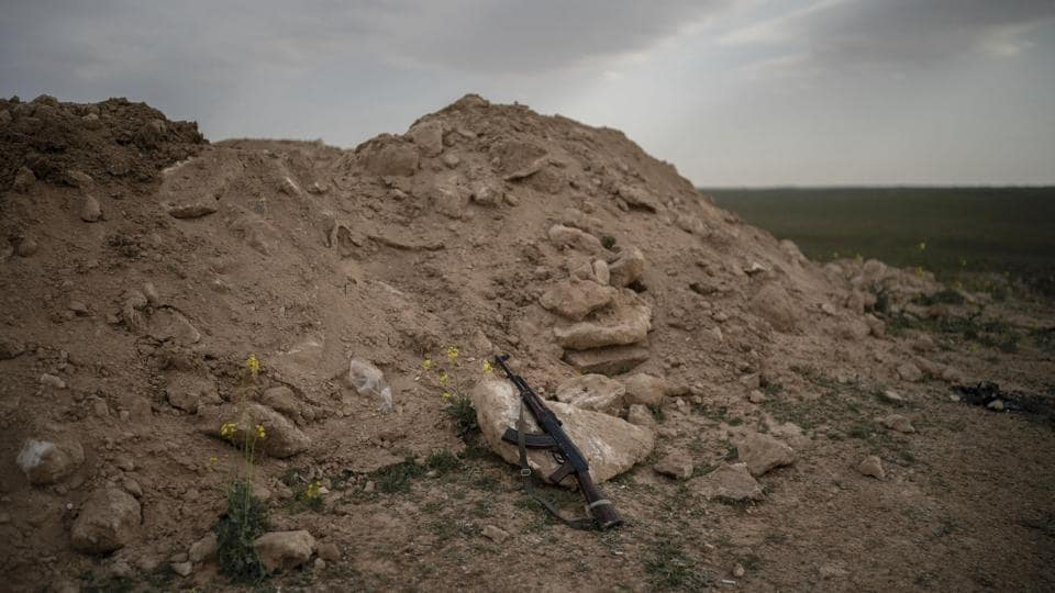 An AK-47 rifle, belonging to an SDF fighter, rests on a rock on a hill in the desert outside the village of Baghouz. Activists said a truce in place has been extended for five days as of Sunday. A person familiar with ongoing deliberations said the group has asked for an exit through a corridor to the rebel-held northwestern province of Idlib and demand to be allowed to leave along with the civilians. (Felipe Dana / AP)