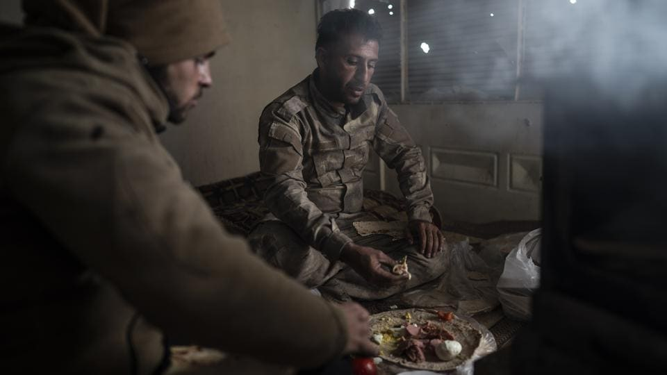 "SDF fighters eat in a building as the fight against Islamic State militants continues. The SDF appears to be aiming to wait the militants out. ""They don't have supplies in the area they are in that would last for a week or more,"" said Baran, the commander. (Felipe Dana / AP)"