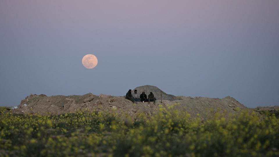 The moon rises behind SDF fighters at a defence post in the desert near the last land still held by Islamic State militants outside Baghouz. Over 30,000 people who left the last IS-held areas have arrived at the al-Hol camp in Syria's northern Hassakeh province in the last few weeks, raising the overall population of the camp to almost 42,000. (Felipe Dana / AP)