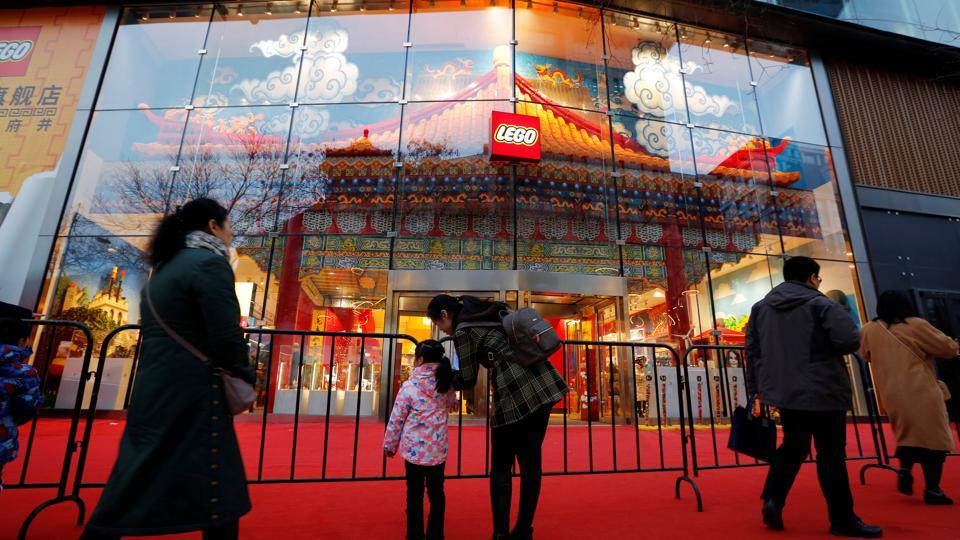 A woman talks to a girl outside the newly opened flagship store of Danish toymaker Lego near Wangfujing shopping street in Beijing on February 22.