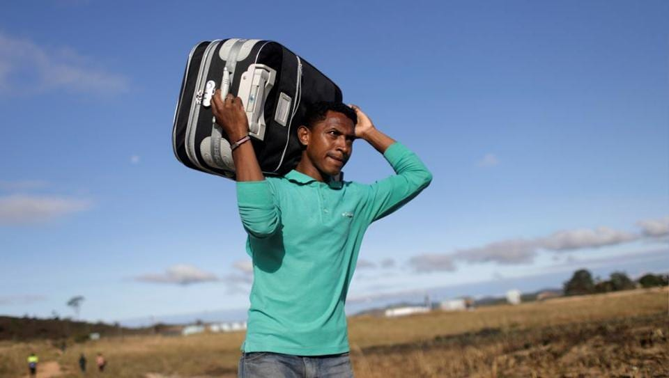 A man carries his suitcase through a field as he tries to cross the border between Venezuela and Brazil in Pacaraima, Roraima state, Brazil. Venezuelans frustrated over their nation's crippling food and medical shortages are expected to join opposition leaders Saturday in a potentially risky push to deliver international aid that Nicolas Maduro has refused to accept into the country. (Ricardo Moraes / REUTERS)