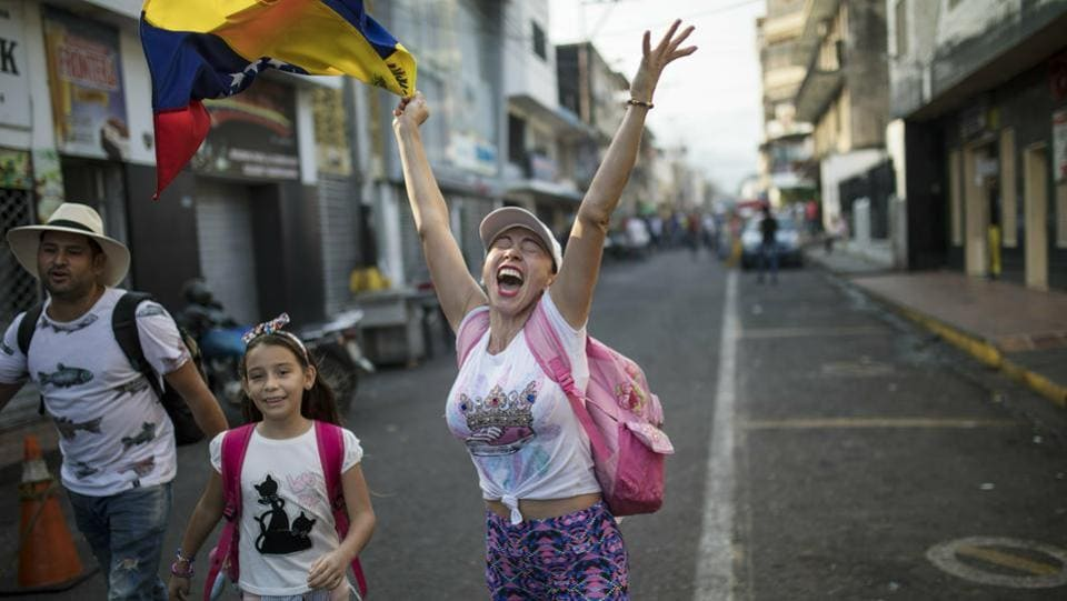 "A woman shouts ""Freedom!"" as she walks with her family towards the Venezuela Aid Live concert on the Colombian side of the border. The opposition is planning to hold three simultaneous aid pushes on Saturday. Aside from the events in Colombia, they also hope to get humanitarian assistance delivered by sea and through Venezuela's remote border with Brazil. (Rodrigo Abd / AP)"