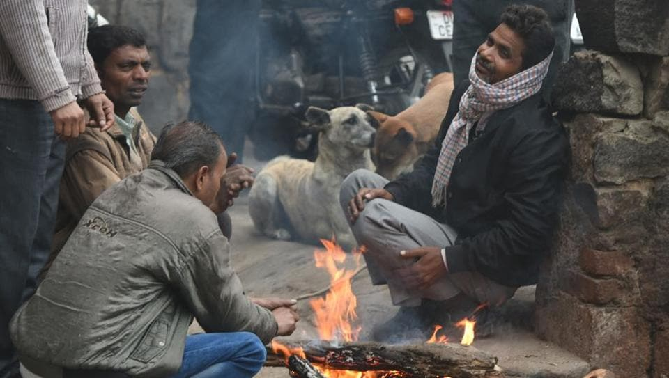 People seen sitting near bonfire to keep themselves warm on a cold winter morning at I.P.Extension, in New Delhi