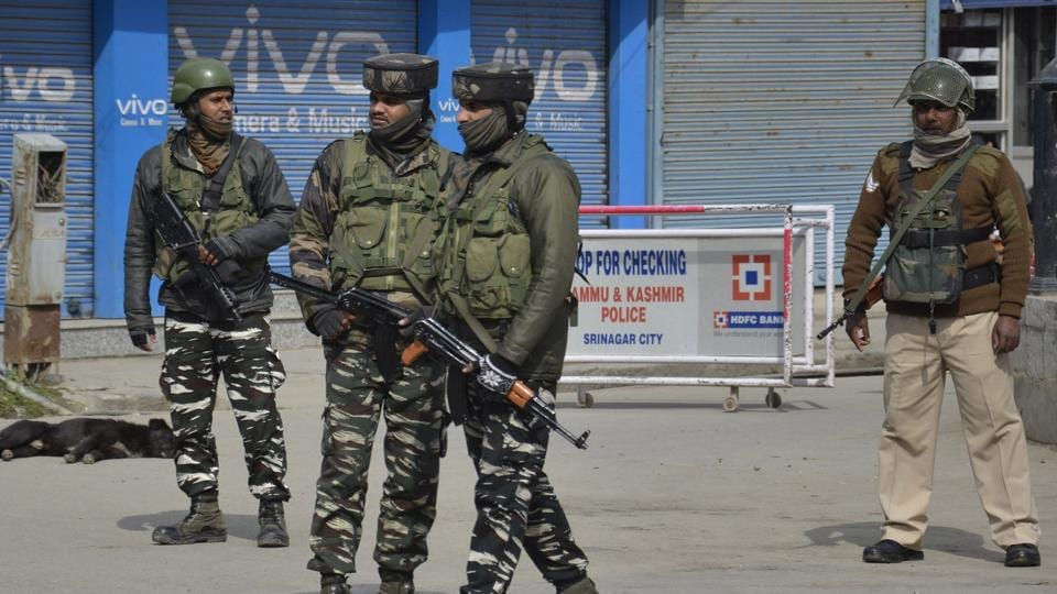 Central Reserve Police Force (CRPF) personnel stand guards during restrictions in Downtown area of Srinagar on Sunday.