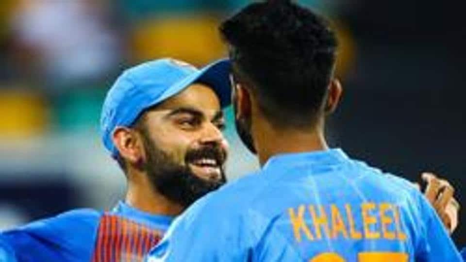 Virat Kohli (L) congratulates teammate Khaleel Ahmed on dismissing Australia's batsman D'Arcy Short.