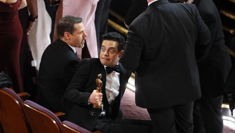 Best Actor winner Rami Malek reacts after falling down the stairs on the stage.