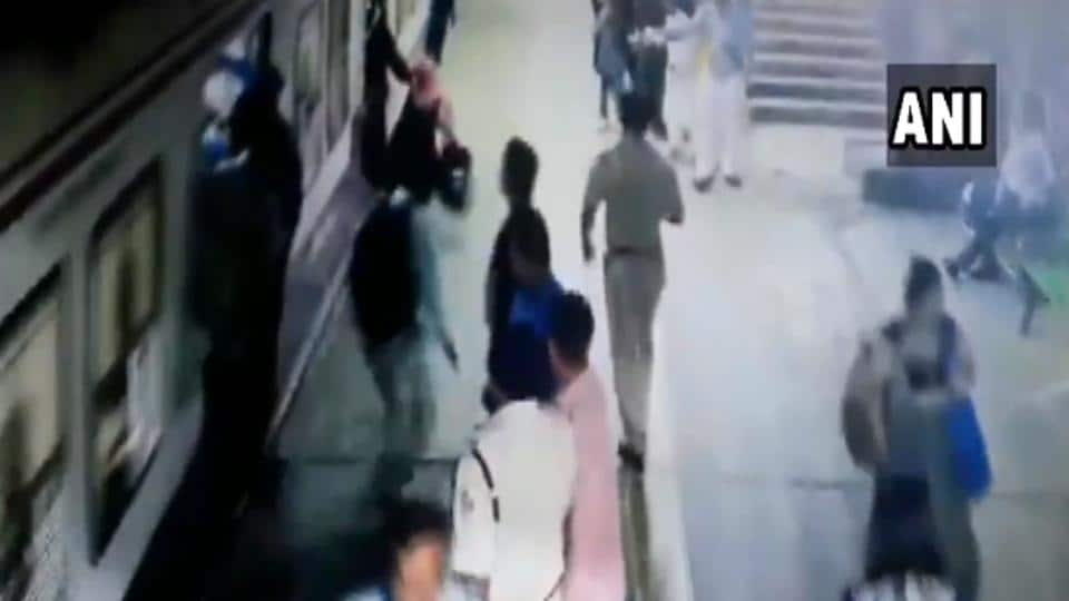 The woman fell down while trying to board the moving train.