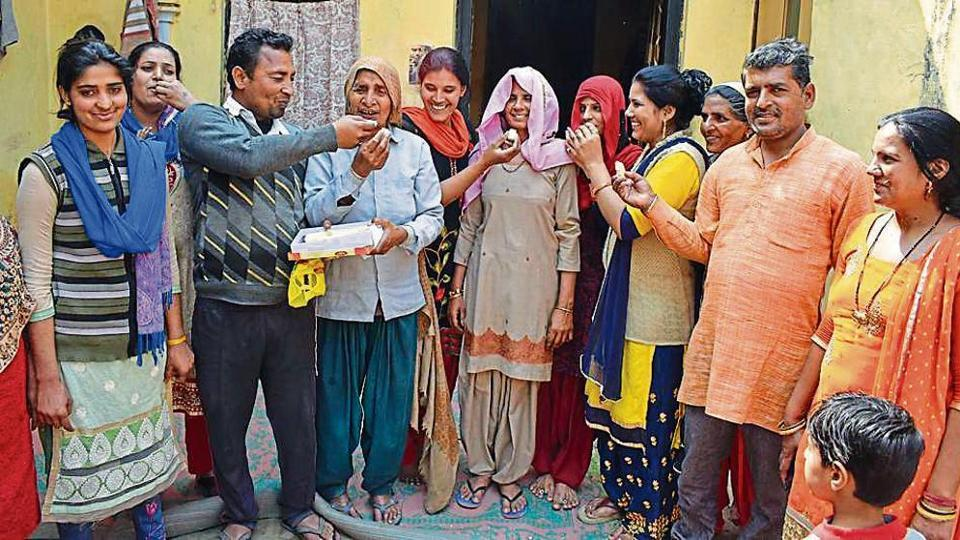 Sneha and Suman's family members celebrate in their village Kathikhera in Hapur district of Uttar Pradesh on Monday.