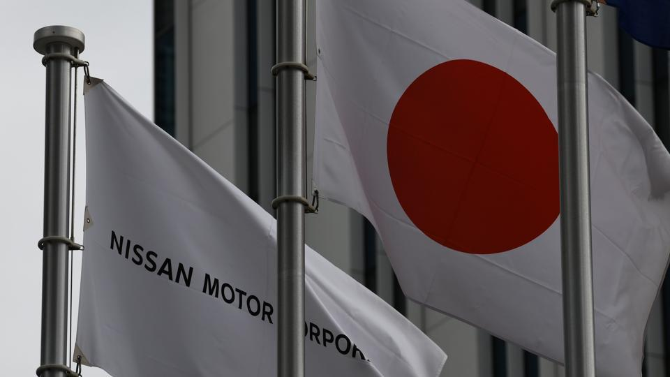 The Nissan flag is hosted beside Japan's national flag in front of the headquarters of Japanese auto maker Nissan in Yokohama, suburban Tokyo on February 12.