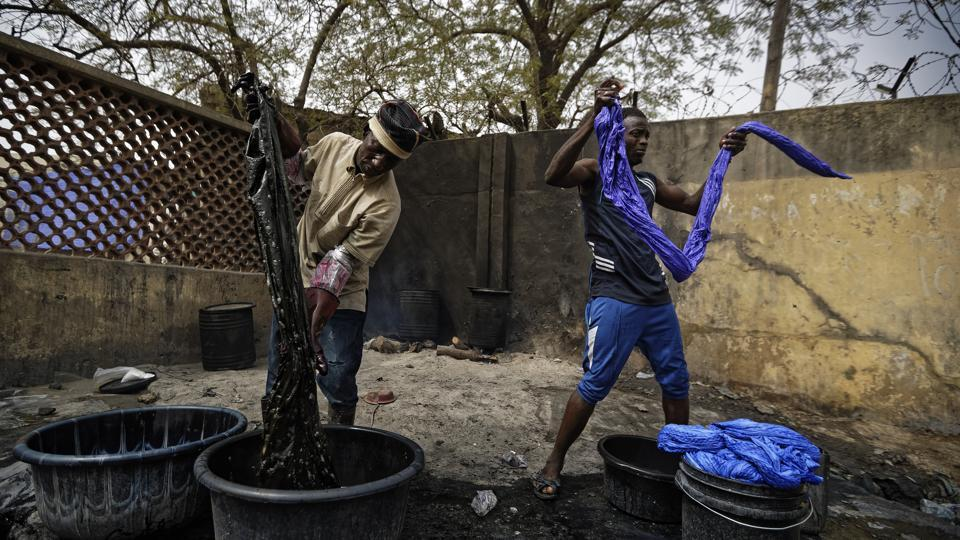 The preparation of the indigo dye takes up to a pungent month, then fabric is soaked for up to several hours for the darkest hues. The men periodically lift the fabric from the pits to drip, saying the process needs to breathe. A dash of potassium holds the colour in. (Ben Curtis / AP)