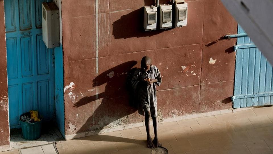 A Quran student, called a talibe, eats as he begs in front of a hotel in Saint-Louis, Senegal. An eight-year-old boy fled his Quranic school in Saint-Louis, Senegal this month after he said a teacher threatened to beat him for not earning enough money begging on the street. Hours later, alone in the corner of a low-lit bus station, he was raped by a teenager. (Zohra Bensemra / REUTERS)