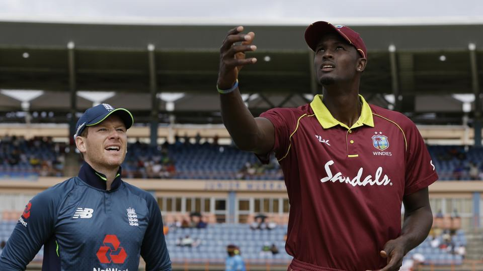 West Indies' captain Jason Holder flips the coin as England's captain Eoin Morgan looks on prior to the third ODI.