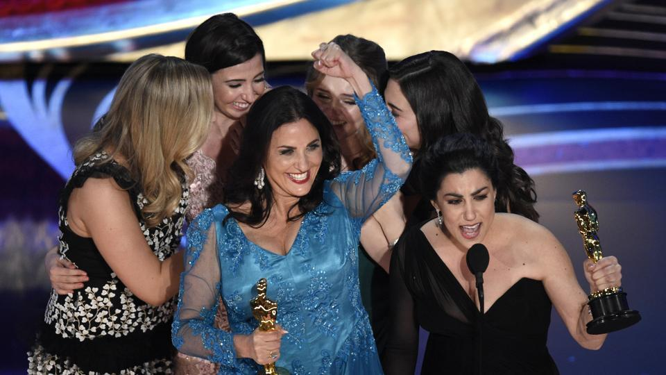 Melissa Berton (centre left) and Rayka Zehtabchi accept the award for best documentary short for Period. End of Sentence. at the Oscars on February 24, 2019 in Los Angeles.