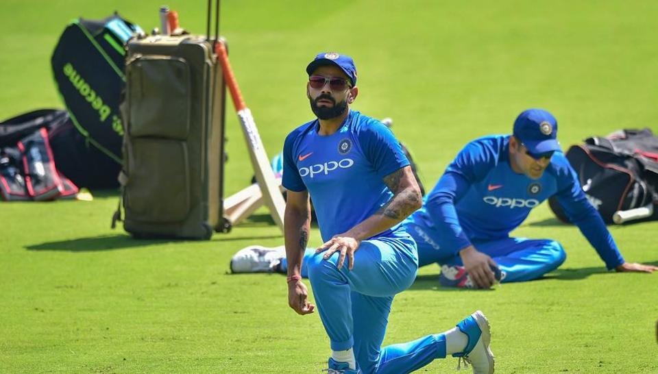 Indian cricket team captain Virat Kohli and M S Dhoni stretch during a practice session ahead of the 2nd T20 match against Australia, at Chinnaswamy Stadium in Bengaluru, Tuesday, Feb 26, 2019