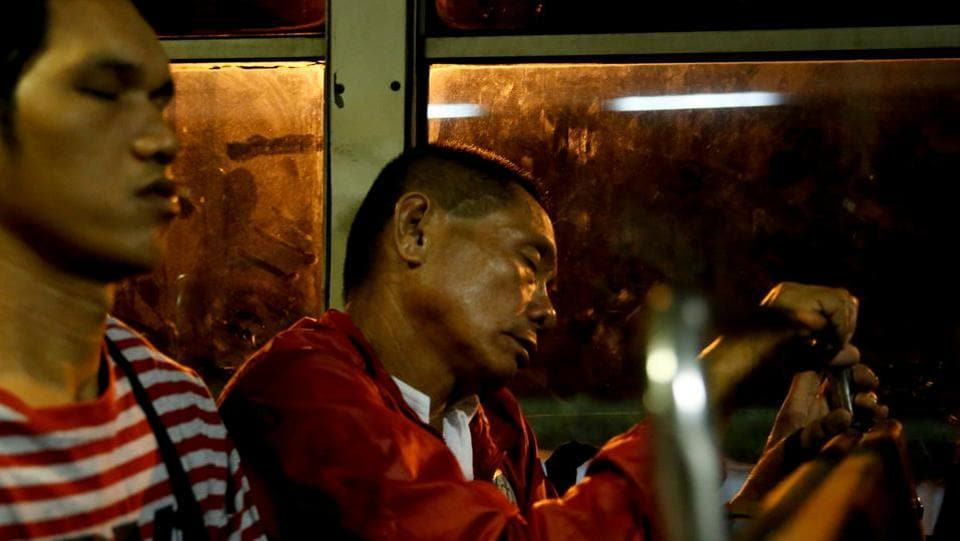 "Alejandro Galasao sleeps on a bus going to work. He has to wake up in the middle of the night for a job that doesn't start until 6 a.m. Galasao only gets four to five hours of sleep each day. ""To be honest, there's really not enough time to sleep. The earliest time I get to sleep is 20:00, sometimes 21:00 and then I have to wake up at 01:00."" (Eloisa Lopez / REUTERS)"