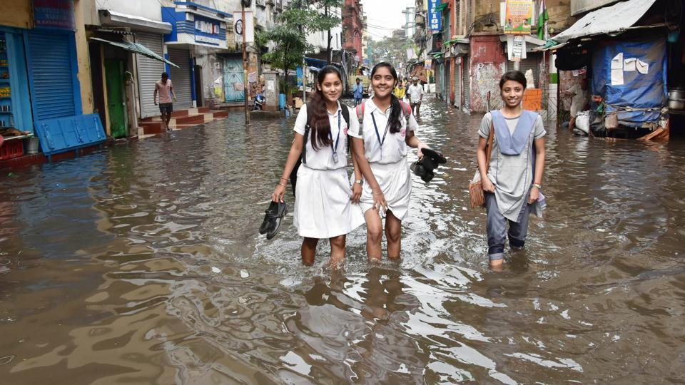 School students crossing the road after water logging in the area due to heavy rain in Kolkata on Thursday.