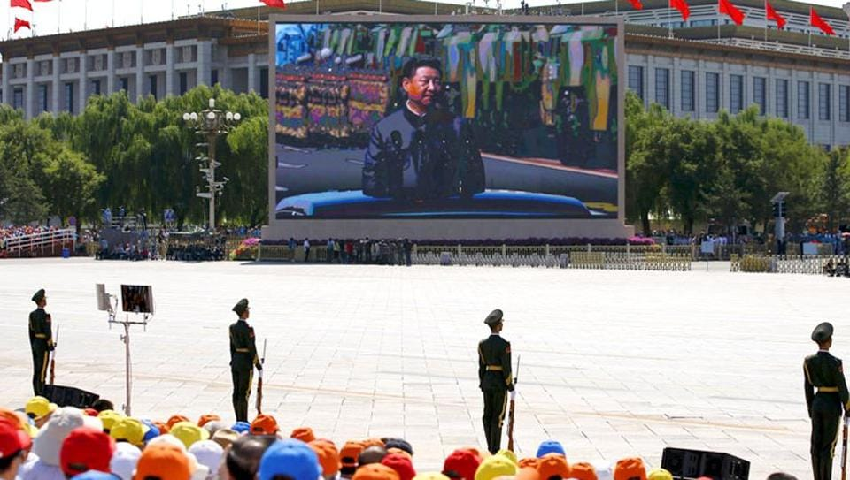 A screen displays Chinese President Xi Jinping reviewing the army at the Tiananmen Square, at the beginning of the military parade.
