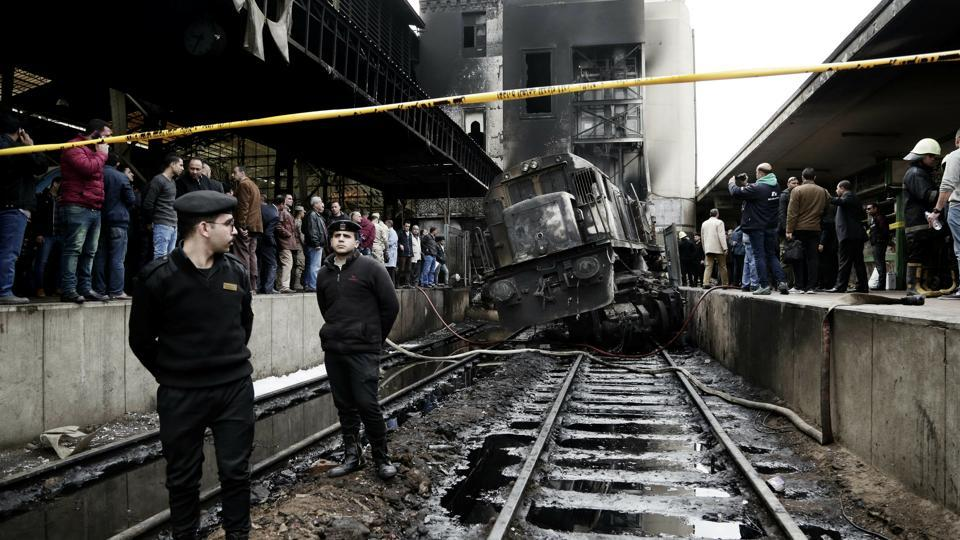 Policemen stand guard in front of a damaged train inside Ramses train station in Cairo, Egypt after at least 20 people were killed and dozens injured when a railcar rammed into a barrier inside the station causing an explosion of the fuel tank and triggering a huge blaze. (Nariman El-Mofty / AP)