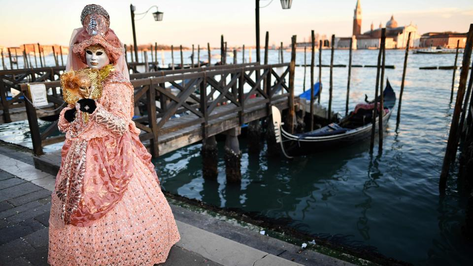 A reveller wearing a mask and a period costume takes part in the Venice Carnival in Venice, Italy. (Alberto Pizzoli / AFP)