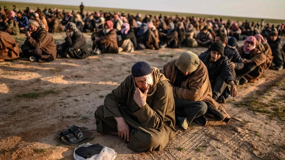 Men suspected of being Islamic State (IS) fighters wait to be searched by members of the Kurdish-led Syrian Democratic Forces (SDF) after leaving the IS group's last holdout of Baghouz, Syria. (Bulent Kilic / AFP)