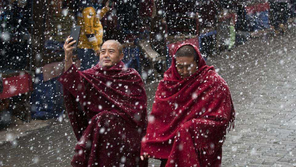An exile Tibetan Buddhist monk uses his phone camera as he walks with another in the snow in Dharmsala, Himachal Pradesh. (Ashwini Bhatia / AP)