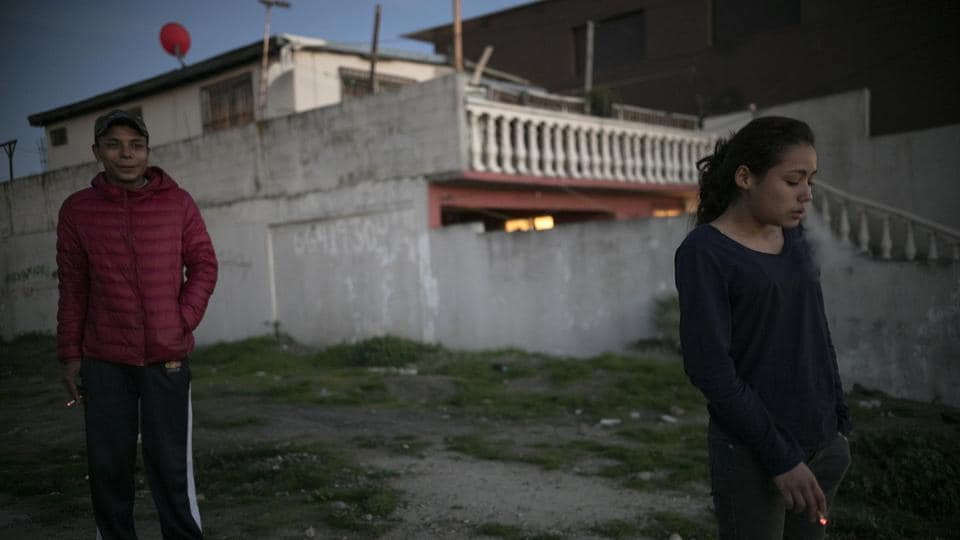 Josue Mejia Lucero (L), smokes along with his girlfriend's sister Xiomara Henriquez Ayala, 13, outside the Agape World Mission shelter. The girls joined the caravan so they could meet their father, who had left them in Mexico's southern border city of Tapachula in August while he tried to get to the United States. (Emilio Espejel / AP)
