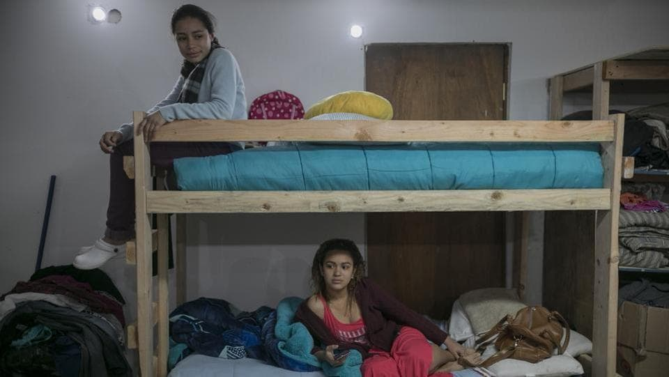 Xiomara Henriquez Ayala sits atop the bunk bed she shares with 18-year-old Valeria Ramos of Honduras, at the Agape World Mission shelter. The sisters fear being deported to El Salvador, though their parents are there. Back home, gang members had beaten up their father and threatened them for walking into what they consider the gang's territory on their way to school. (Emilio Espejel / AP)