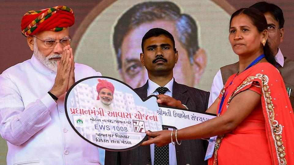 Prime Minister Narendra Modi hands over the key of a house to a beneficiary of the Pradhan Mantri Awas Yojana, in Jamnagar, Gujarat, Monday.