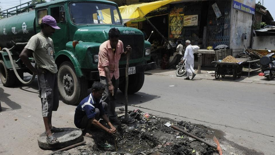 Sanitary workers clear a choked drain, Indore