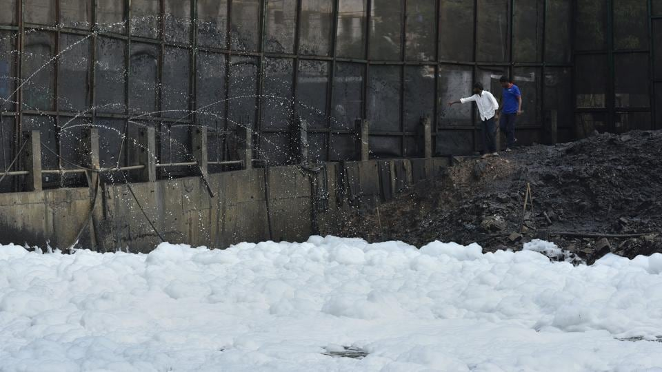 Workers inspecting the sprinklers on the froth filled Bellandur Lake in Bengaluru.