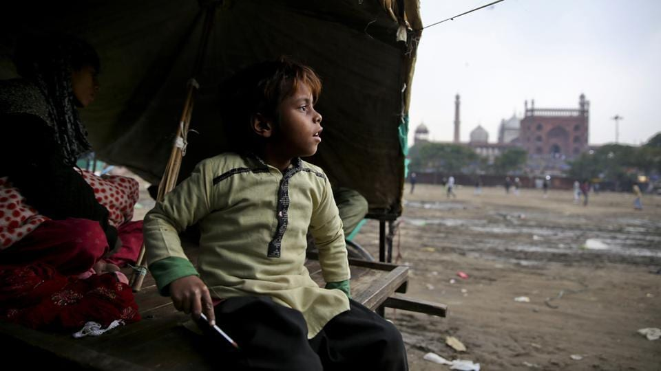 "7-year-old Farmaan looks out from his home, set up on a wooden fruit vendor's cart, as it drizzles in New Delhi. Someday, the family says, the 7-year-old will save them. ""I'll fight,"" the boy's mother said when her husband insisted their son start working. She vowed he would stay in school, no matter what. (Altaf Qadri / AP)"